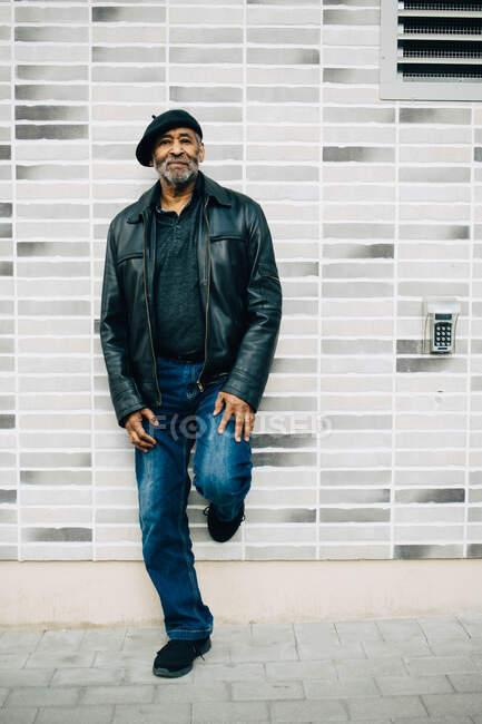 Comprimento total do homem sênior em pé contra a parede — Fotografia de Stock