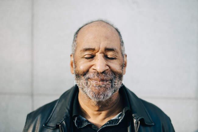 Homme âgé souriant avec les yeux fermés contre le mur — Photo de stock
