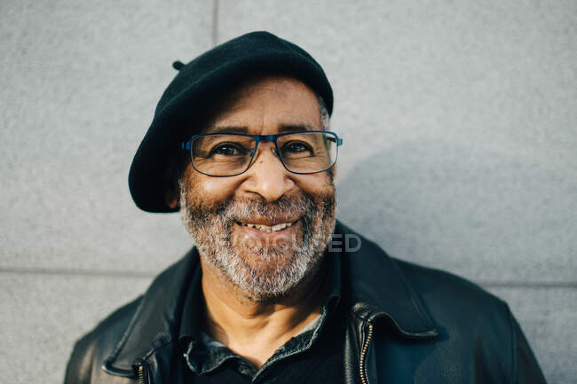 Portrait of smiling senior man against wall — Stock Photo
