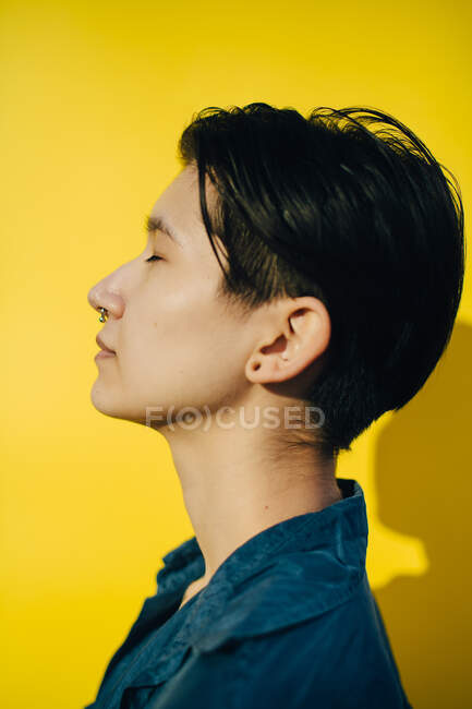 Vista laterale della giovane donna contro sfondo giallo — Foto stock