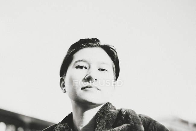Ritratto di giovane donna contro il cielo, bianco e nero — Foto stock