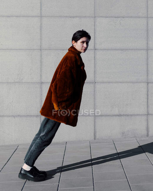 Portrait of contemplating woman with hands in pockets leaning against wall — Stock Photo