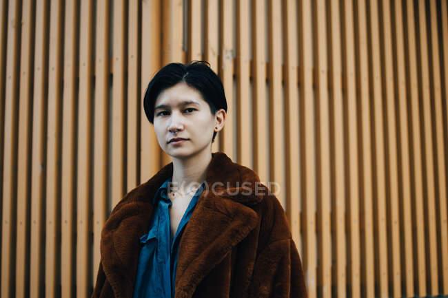 Retrato de mulher em pé contra a parede de madeira — Fotografia de Stock