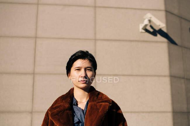 Retrato de mulher em pé contra a parede — Fotografia de Stock