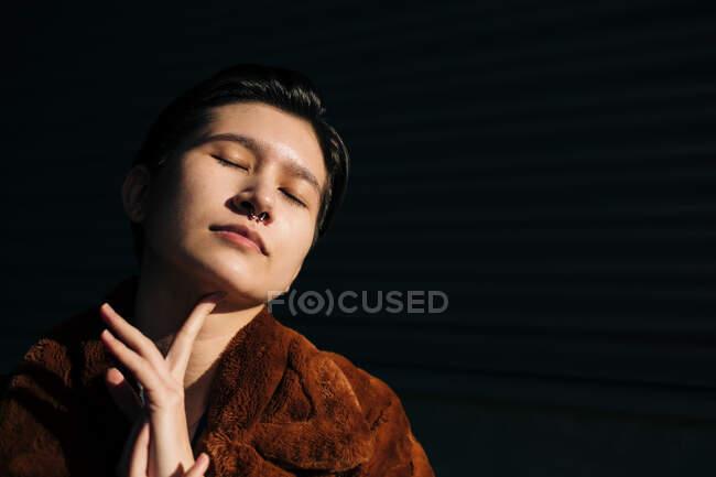 Femme avec les yeux fermés debout sur fond noir — Photo de stock
