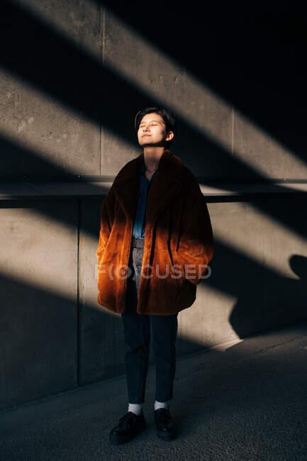 Contemplando jovem mulher com os olhos fechados de pé contra a parede — Fotografia de Stock