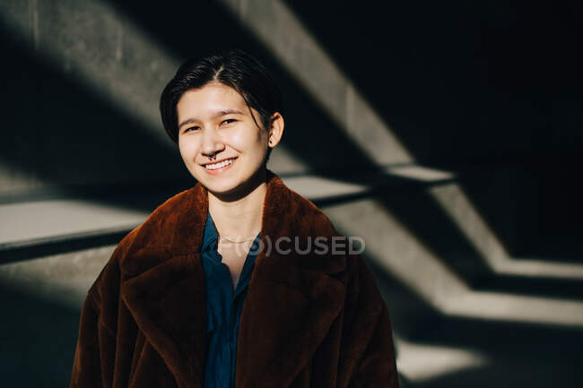 Retrato de jovem sorridente em pé contra a parede — Fotografia de Stock