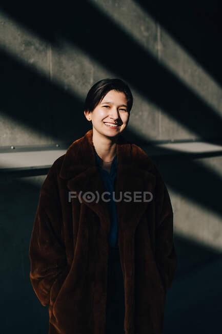 Ritratto di giovane donna felice in piedi contro il muro — Foto stock