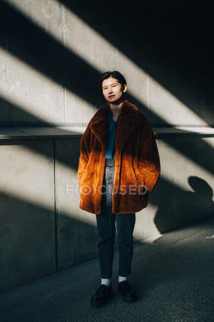 Retrato de contemplar jovem mulher de pé contra a parede — Fotografia de Stock