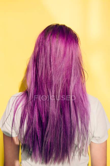 Visão traseira da menina adolescente em pé contra fundo amarelo — Fotografia de Stock