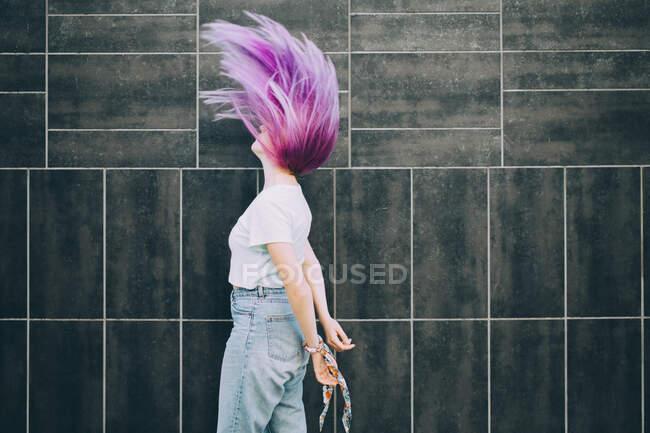 Vista lateral da menina adolescente saltando contra a parede — Fotografia de Stock