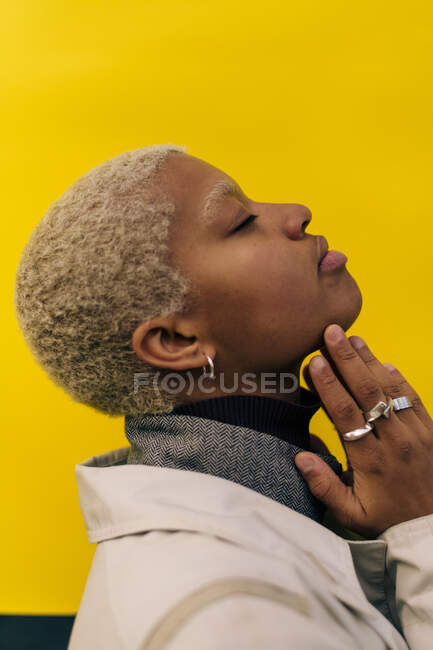 Side view of contemplating young female with eyes closed standing against yellow background — Stock Photo