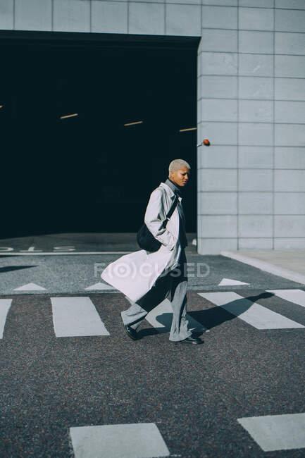 Giovane donna con le mani in tasche che attraversano la strada durante il giorno di sole — Foto stock