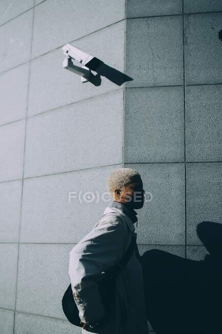 Jeune femme debout contre le mur — Photo de stock