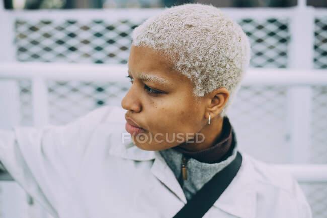 Betrachtet junge Frau, die wegschaut, während sie gegen Geländer sitzt — Stockfoto