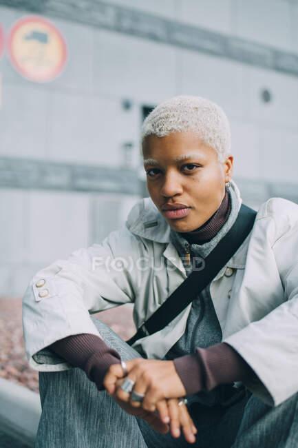 Retrato de jovem mulher confiante sentada contra a parede — Fotografia de Stock