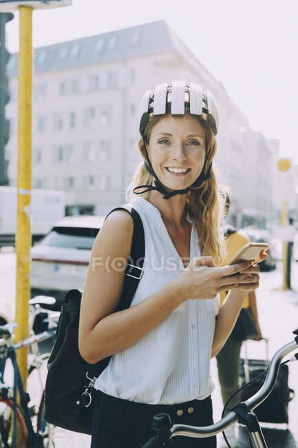 Portrait d'une femme d'affaires souriante utilisant un téléphone portable tout en restant debout en ville — Photo de stock