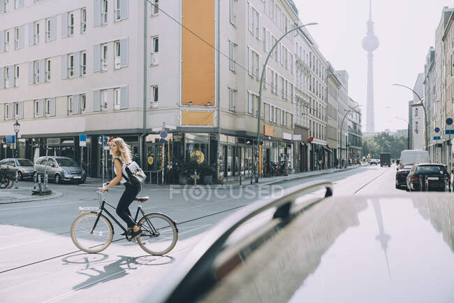 Longitud completa de la bicicleta de equitación ejecutiva femenina en la calle en la ciudad - foto de stock
