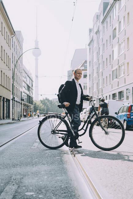 Longitud completa de hombre de negocios con bicicleta en la carretera en la ciudad - foto de stock
