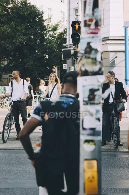 Business people with bicycle waiting for traffic signal in city — Stock Photo