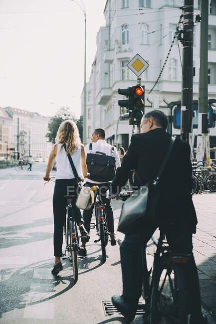 Полная длина деловых коллег, катающихся на велосипеде по улице в городе — стоковое фото
