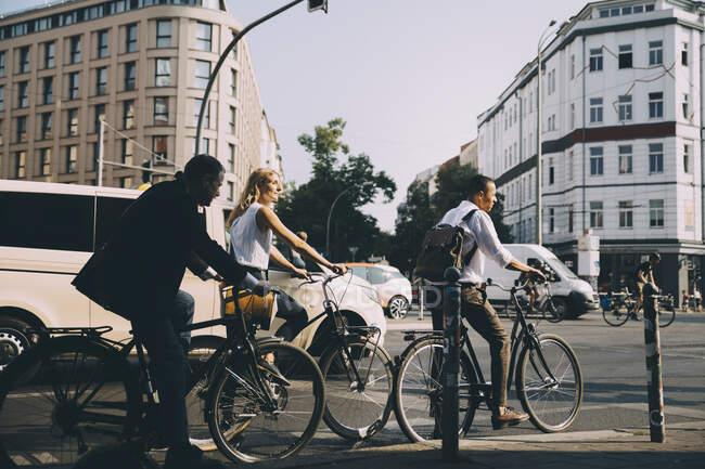 Полная длина деловых коллег, едущих на велосипедах против строительства в городе — стоковое фото