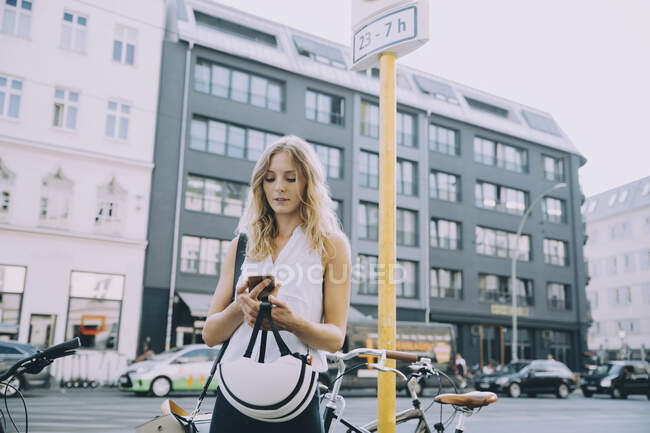 Young businesswoman using mobile phone while standing on street in city — Stock Photo