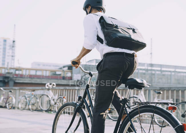 Rear view of businessman with backpack riding bicycle on sidewalk in city — Stock Photo