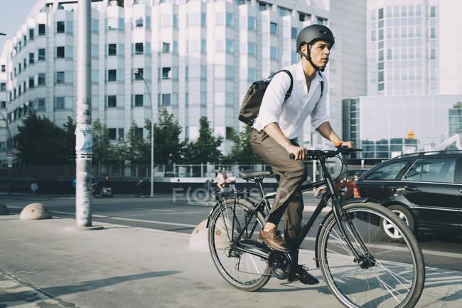 Piena lunghezza di uomo d'affari in bicicletta sul marciapiede contro edificio in città — Foto stock