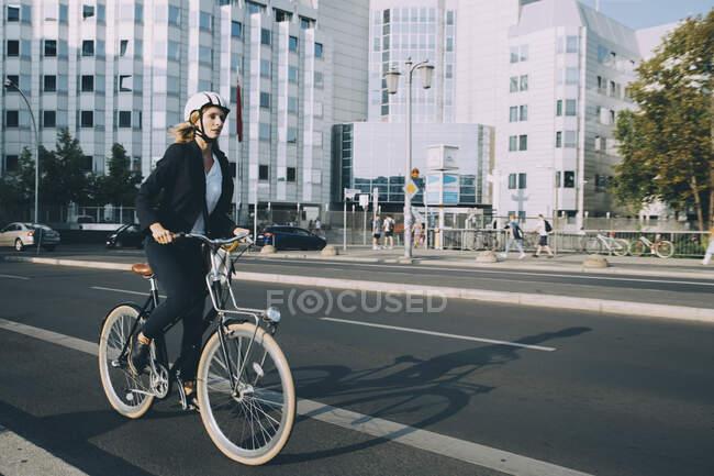 Longitud completa de la mujer joven con casco de montar en bicicleta en la calle en la ciudad - foto de stock
