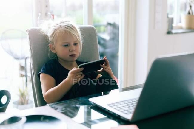Chica navegando por la red en el teléfono inteligente mientras está sentado junto a la mesa en casa - foto de stock