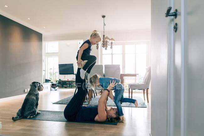 Lächelnde Mutter hebt glückliche Töchter an, während sie zu Hause auf der Gymnastikmatte liegt — Stockfoto