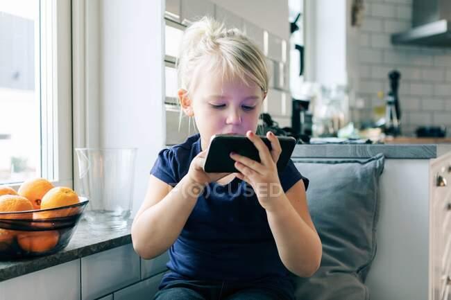 Chica surfeando red mientras está sentado por la ventana en casa - foto de stock