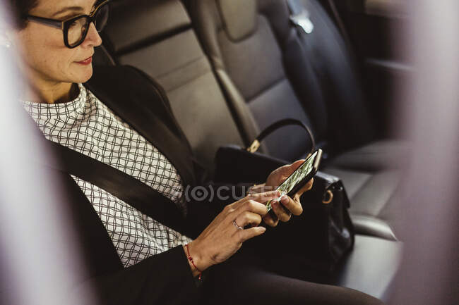 Female entrepreneur using device screen while sitting in car — Stock Photo