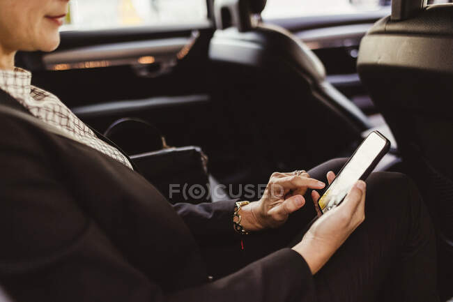 Midsection of entrepreneur surfing net while sitting in car — Stock Photo