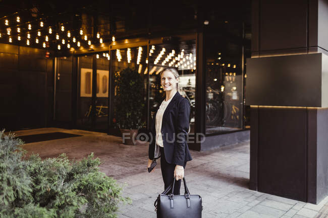 Portrait of female entrepreneur with bag standing at building entrance — Stock Photo