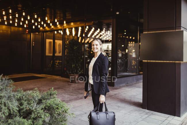 Ritratto di imprenditrice femminile con borsa in piedi all'ingresso dell'edificio — Foto stock