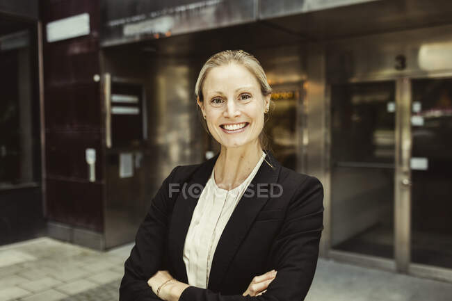 Portrait of confident female entrepreneur with arms crossed standing against building — Stock Photo