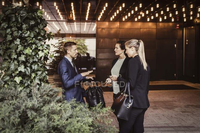 Männlicher Unternehmer diskutiert mit Mitarbeitern, während er am Hauseingang steht — Stockfoto