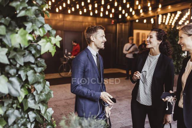 Männlicher Unternehmer lächelt mit Mitarbeitern, während er am Hauseingang steht — Stockfoto