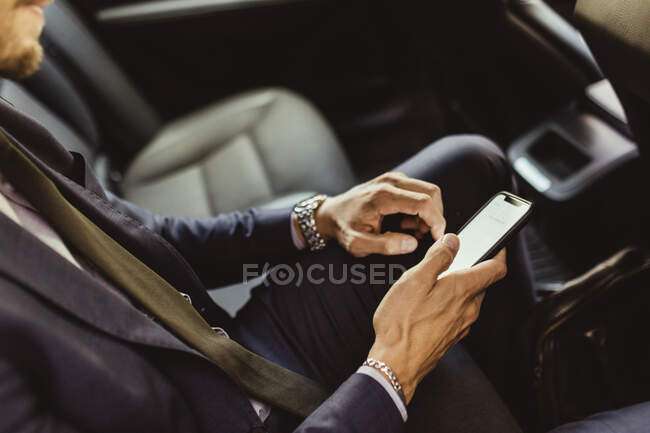 Midsection of business man using device screen while sitting in car - foto de stock