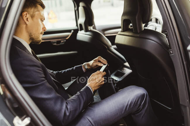 Side view of businessman using smart phone while sitting in car — Stock Photo