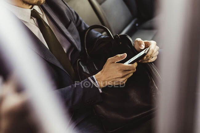 Midsection of businessman using smart phone while sitting in car — Stock Photo