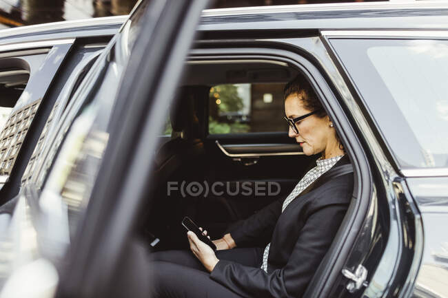 Entrepreneur using smart phone while sitting in car — Stock Photo