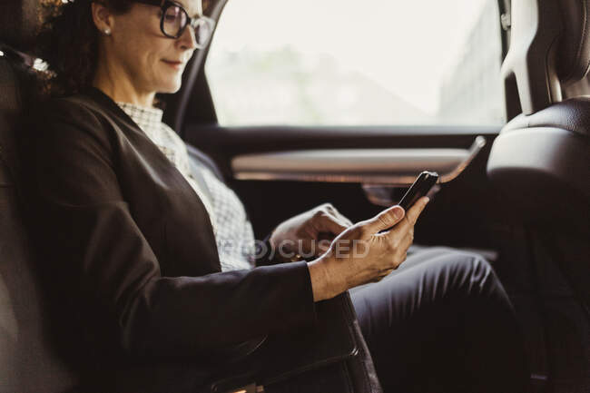 Entrepreneur using mobile phone while sitting in car — Stock Photo