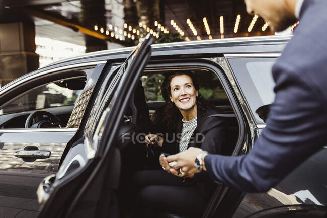 Smiling female entrepreneur looking at male coworkers while sitting in car. - foto de stock