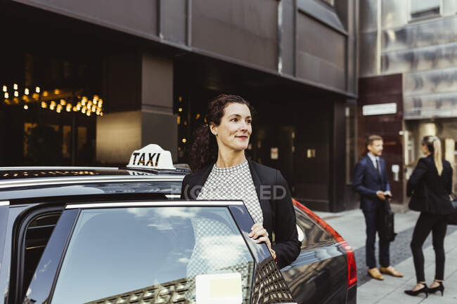 Smiling female entrepreneur looking away while entering in taxi. - foto de stock