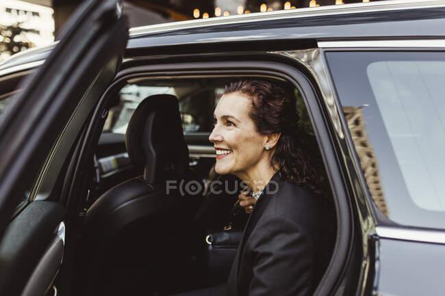 Усміхаючись, жінка - підприємець озирається геть, виходячи з машини. — стокове фото