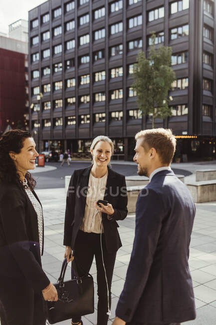 Smiling male and female entrepreneurs standing outdoors — Stock Photo