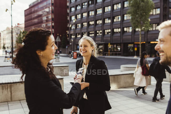 Female entrepreneur smiling with coworkers while standing outdoors — Stock Photo